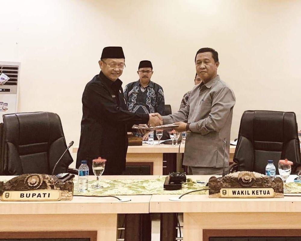 Pimpinan sidang paripurna H Hapis Hasbiallah menyerahkan dokumen pandangan umum fraksi kepada Bupati, H Cek Endra