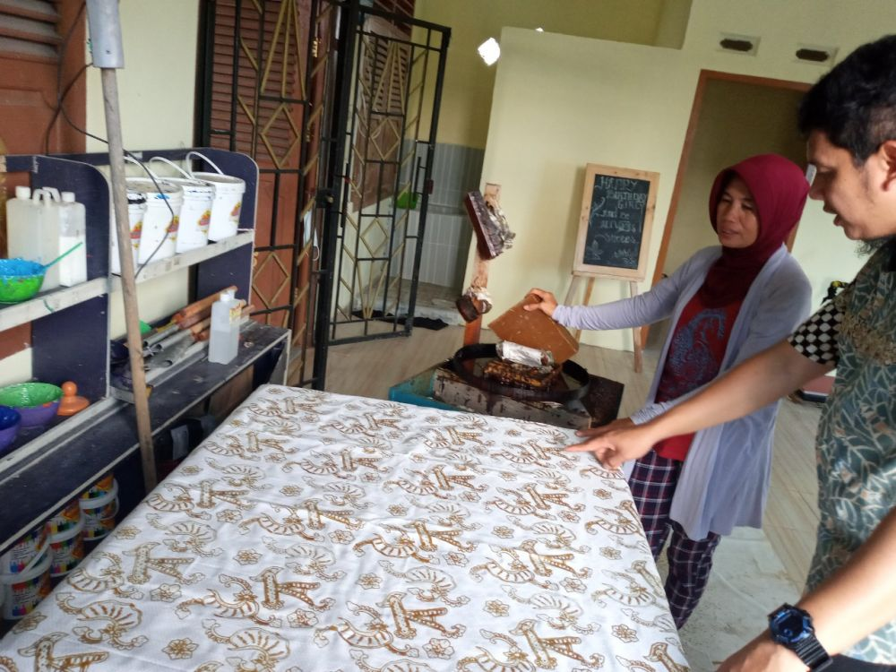 Legal and Relation Assistant Manager Jambi Field, Ari Rachmadi dan Ketua Kelompok Batik Serumpun Berlian, Tinah berbincang terkait motif batik.