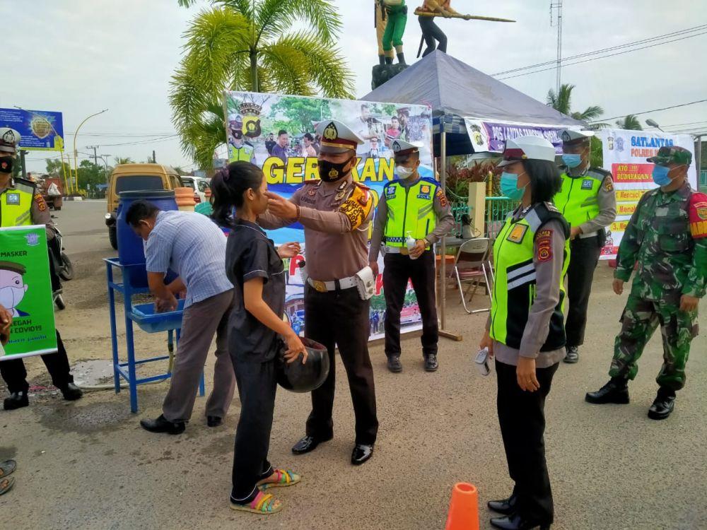 Satlantas polres Muarojambi membagikan masker ke pengendara.