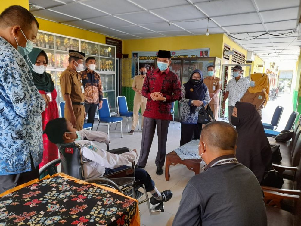 Ketua DPRD Provinsi Jambi Edi Purwanto menyerahkan bantuan kursi roda kepada Anugrah Alfitrah, siswa kelas 7 SMP Negeri 6 Kota Jambi, Senin (19/4/2021).