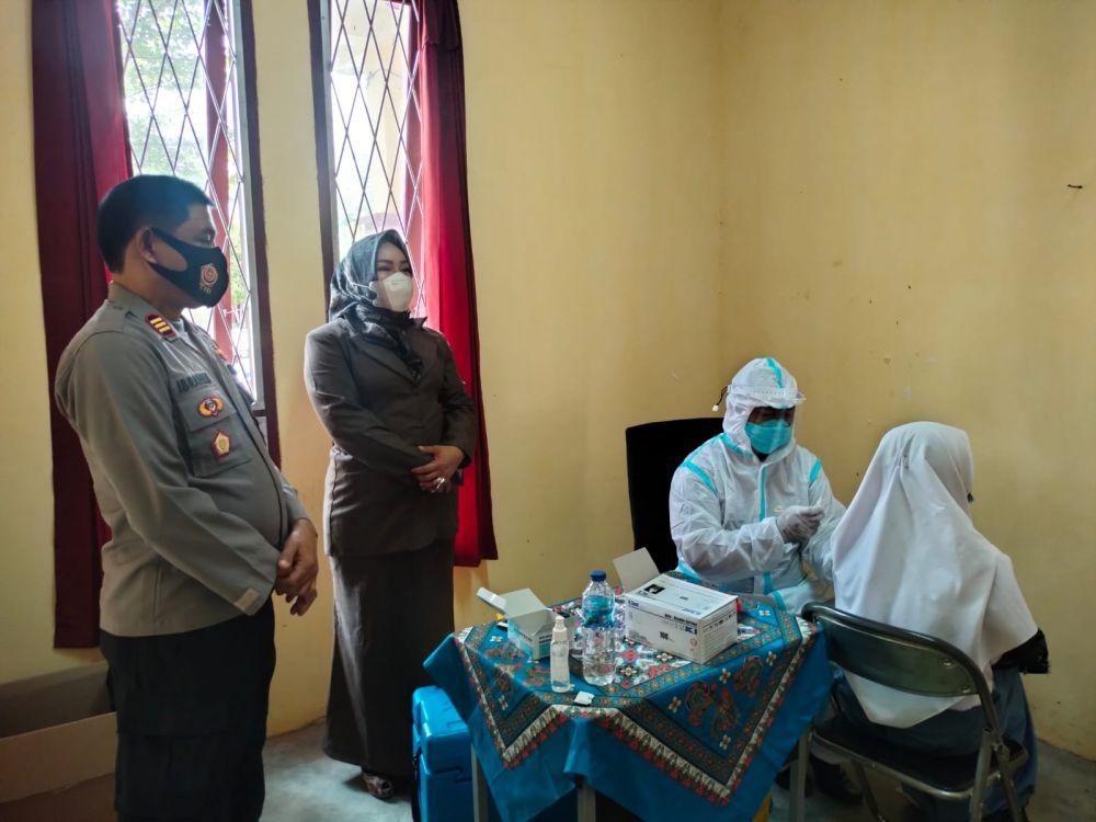Kepsek SMKN 5 Tebo mendampingi Kapolsek Rimbo Ilir AKP Ibrahim mengecek pelaksanaan vaksinasi.