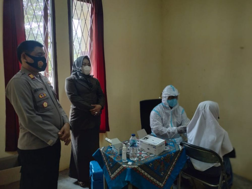 Kepala SMKN 5 Ramayani M.PD mendampingi Kapolsek Rimbo Ilir AKP Ibrahim mengecek pelaksanaan vaksinasi covid 19